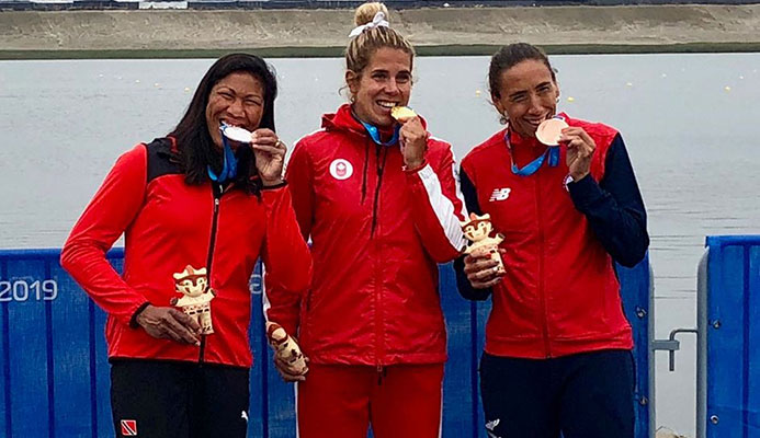 T&T's rower silver medallist Felice Aisha Chow, left, gold medallist Jessica Sevick of Canada, centre, and Chile's Soraya Jadue, the bronze medallist, bite down on their medals after the presentation ceremony for the women's singles sculls at the Pan American Games in Lima Peru on Friday.