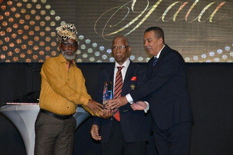 "RESPECTED LEADER, ADMINISTRATOR AND MOTIVATOR: In one of his rare public appearances in his last years, former Olympic Committee president Alexander Chapman, centre, joined President Anthony Carmona, right, in presenting the Alexander B Chapman Award to football coach Anthony ""Dada""   Photo: ISHMAEL SALANDY"